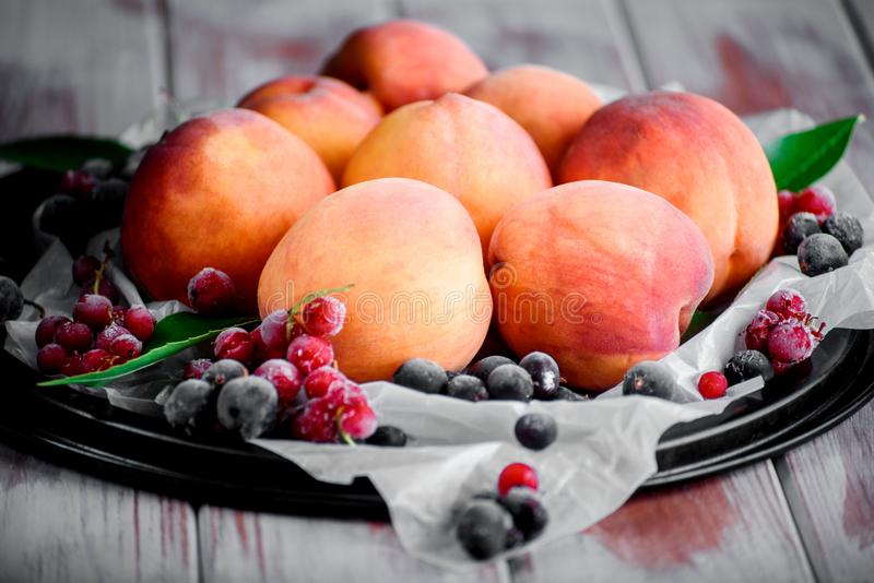 Rijpe perzik met bessen op de lijst stock foto