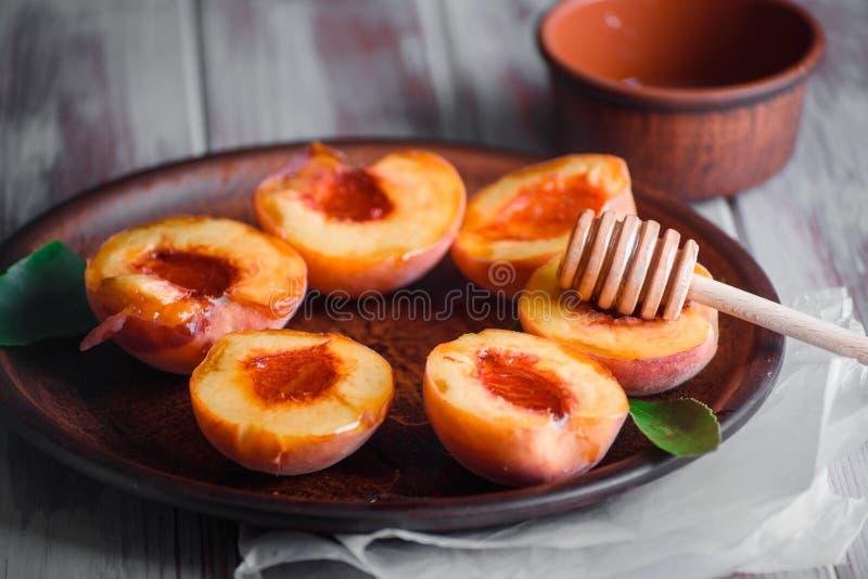 Rijpe perziken op een lijst met smakelijke honing stock afbeeldingen