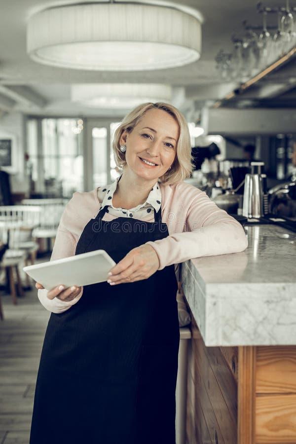Rijpe prettige blonde-haired vrouw die zich in haar eigen restaurant bevinden royalty-vrije stock foto's