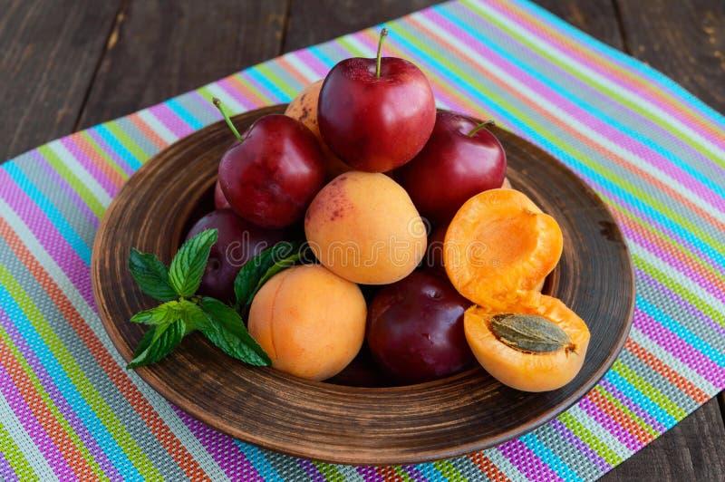 Rijpe pruimen (verscheidenheid: Reine-claude) en abrikozen in een kleikom op een heldere achtergrond stock foto's