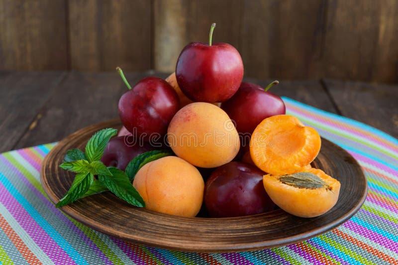 Rijpe pruimen (verscheidenheid: Reine-claude) en abrikozen in een kleikom op een heldere achtergrond royalty-vrije stock foto