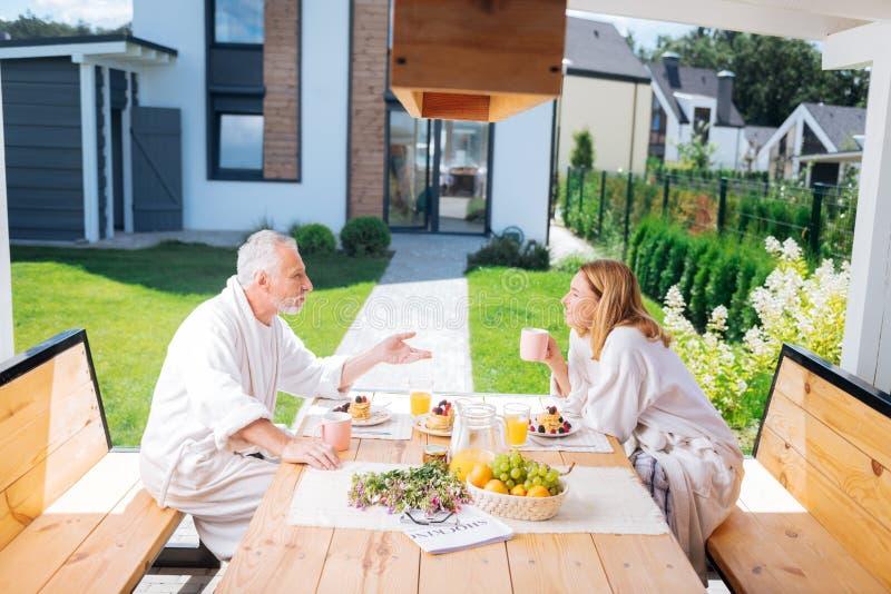 Rijpe richtende vrouw en echtgenoot die witte badjassen dragen die ontbijt hebben stock fotografie