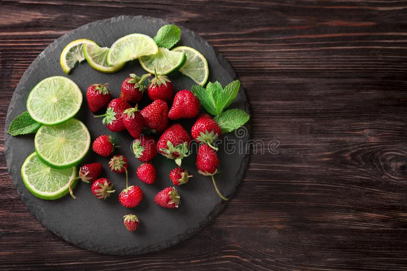 Rijpe rode aardbeien met kalkplakken op leiplaat stock afbeeldingen