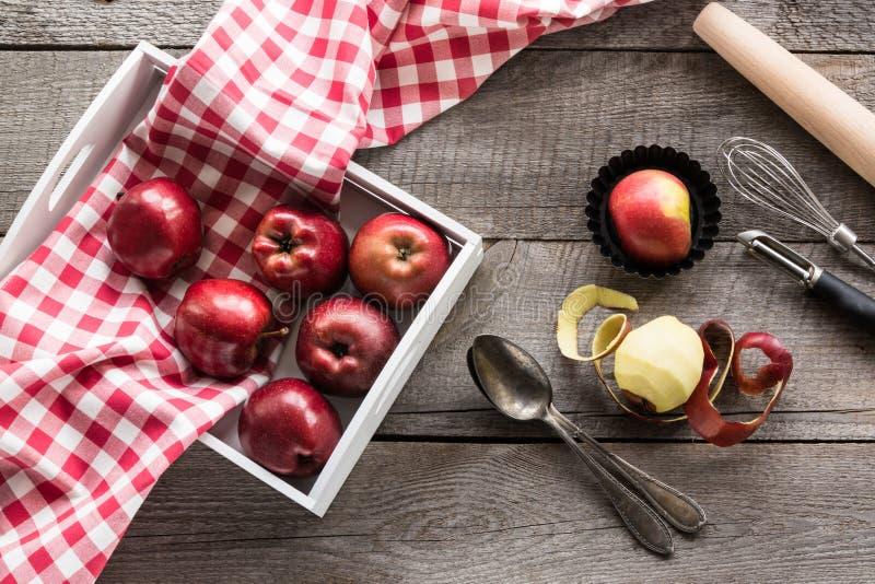 Rijpe rode appelen in berkdienblad op houten raad met rood geruit rond servet, toebehoren voor baksel royalty-vrije stock afbeelding