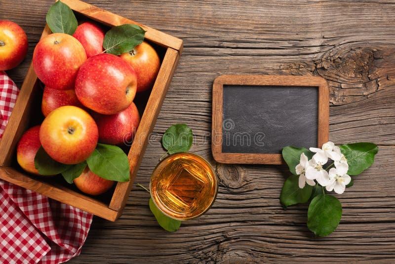Rijpe rode appelen in houten vakje met tak van witte bloemen, glas vers sap en schoolbord op een houten lijst stock foto