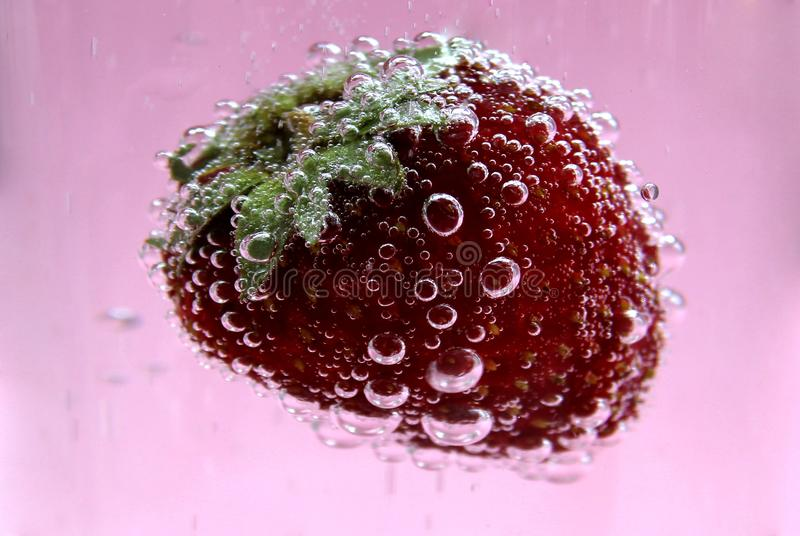 Rijpe rode die aardbeien in het water met bellen wordt behandeld stock foto's