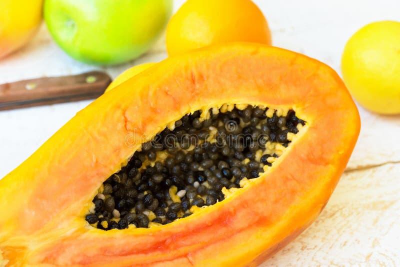 Rijpe sappige besnoeiing in halve oranje de citroen groene appelen van papaja ruwe citrusvruchten op witte houten keukenlijst Gez royalty-vrije stock fotografie
