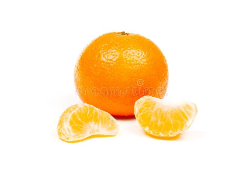 Rijpe sappige die mandarijn in de schil en in plakken op witte achtergrond worden geïsoleerd stock afbeelding