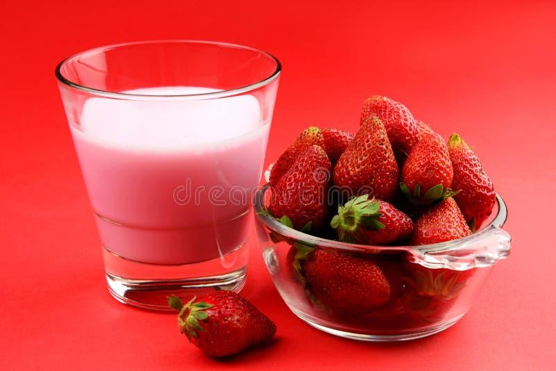 Rijpe Sappige en Verse Aardbei in een kom met een glas van milkshake op rode achtergrond stock foto