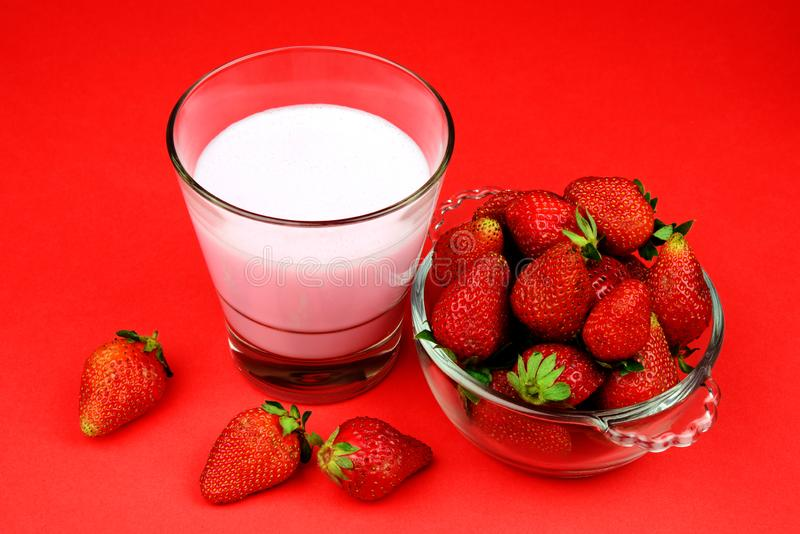 Rijpe Sappige en Verse Aardbei in een kom met een glas van milkshake op rode achtergrond stock foto's