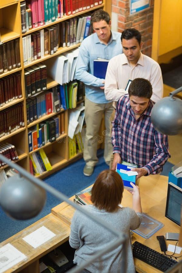 Rijpe studenten bij teller in universiteitsbibliotheek stock fotografie