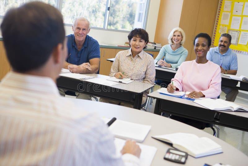 Rijpe studenten en hun leraar in een klaslokaal stock afbeelding