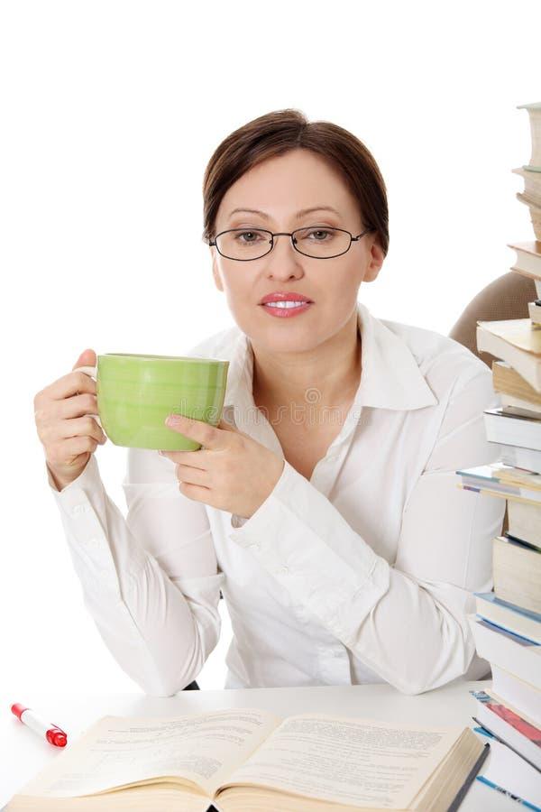 Rijpe studentenvrouw bij het bureau stock fotografie