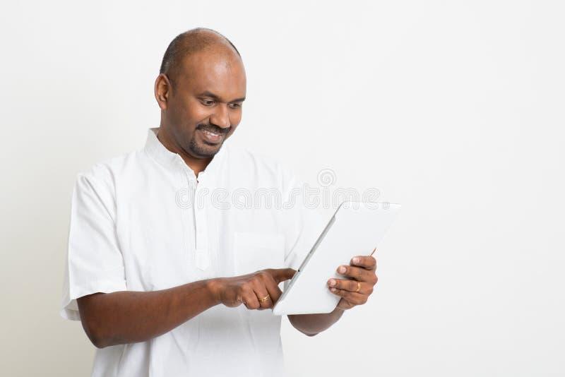 Rijpe toevallige bedrijfs Indische mens die tabletpc met behulp van royalty-vrije stock foto
