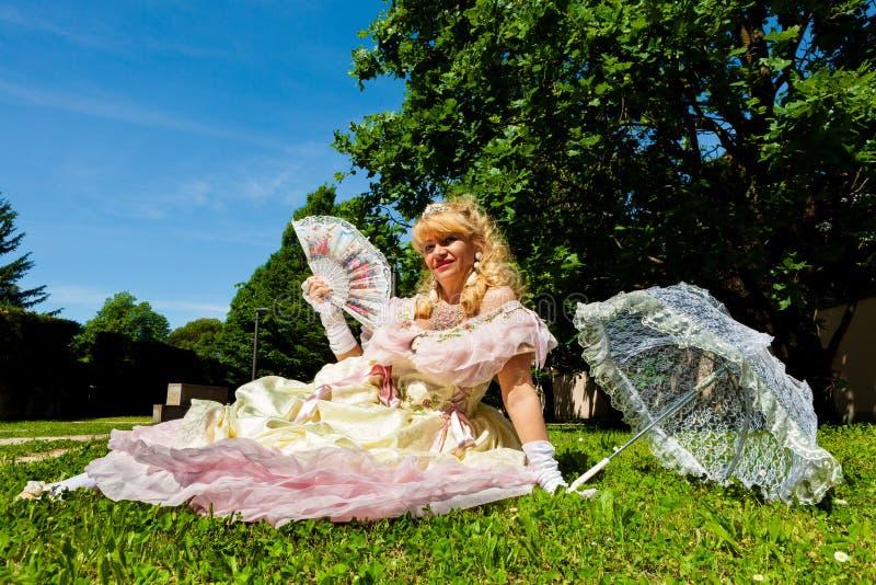 Rijpe uitstekende vrouw in Venetiaans kostuum die op het groene park met witte paraplu liggen stock afbeelding