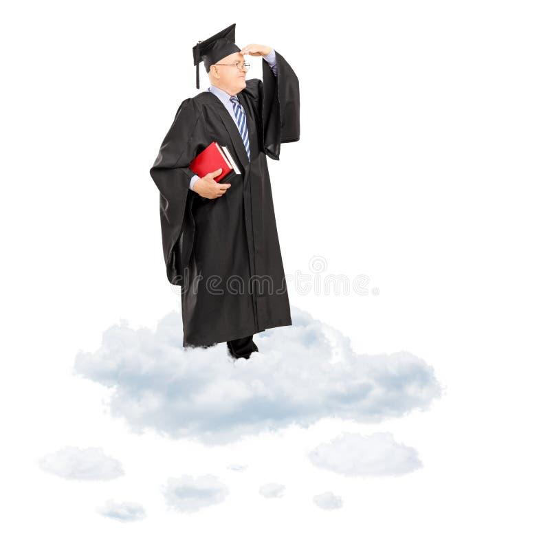 Rijpe universiteitsprofessor in graduatietoga die zich op wolk bevinden stock afbeelding