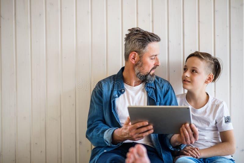Rijpe vader met kleine zoonszitting binnen, gebruikend tablet De ruimte van het exemplaar royalty-vrije stock afbeelding
