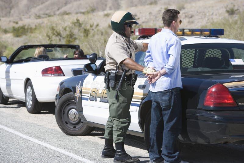 Rijpe Verkeerscop die de Midden Oude Mens arresteren stock fotografie