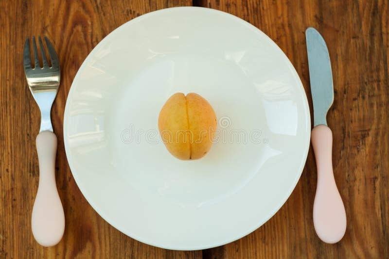 Rijpe verse abrikozenvruchten op een witte plaat op de houten achtergrond Exemplaar ruimte, delisious gezond voedsel stock afbeelding
