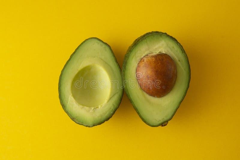 Rijpe verse avocado slaces die op gele achtergrond wordt geïsoleerd Kleurrijke gezonde voedselachtergrond Geïsoleerdeo avocado De royalty-vrije stock afbeeldingen