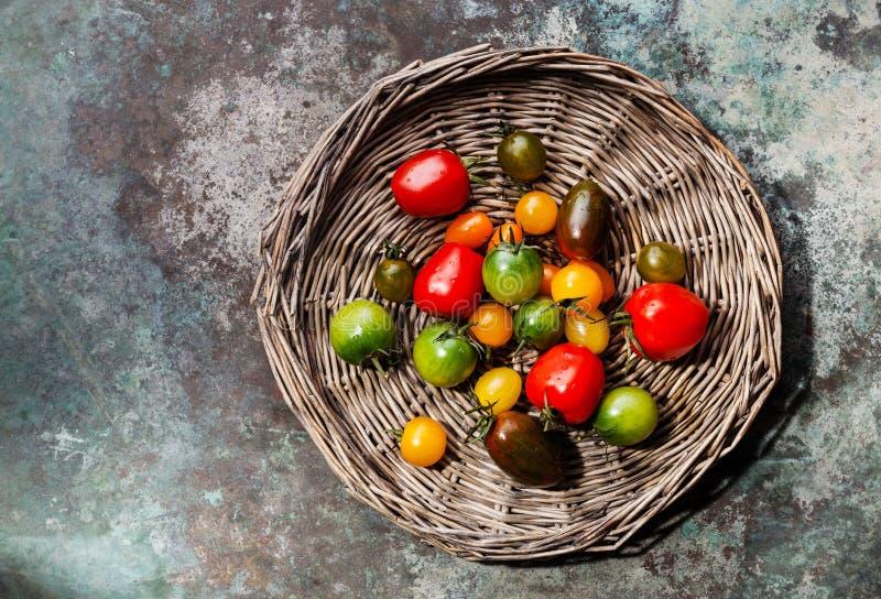 Rijpe verse kleurrijke tomaten op rieten dienblad stock afbeelding