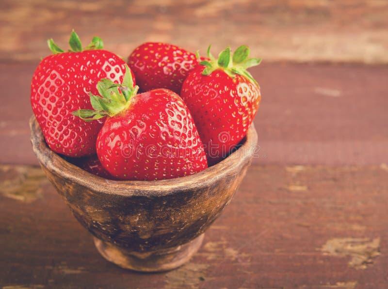 Rijpe verse sappige organische aardbeien in oude kleikom stock fotografie