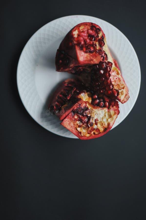 Rijpe versheids rode granaatappel met zaad, korrels op witte plaat stock foto