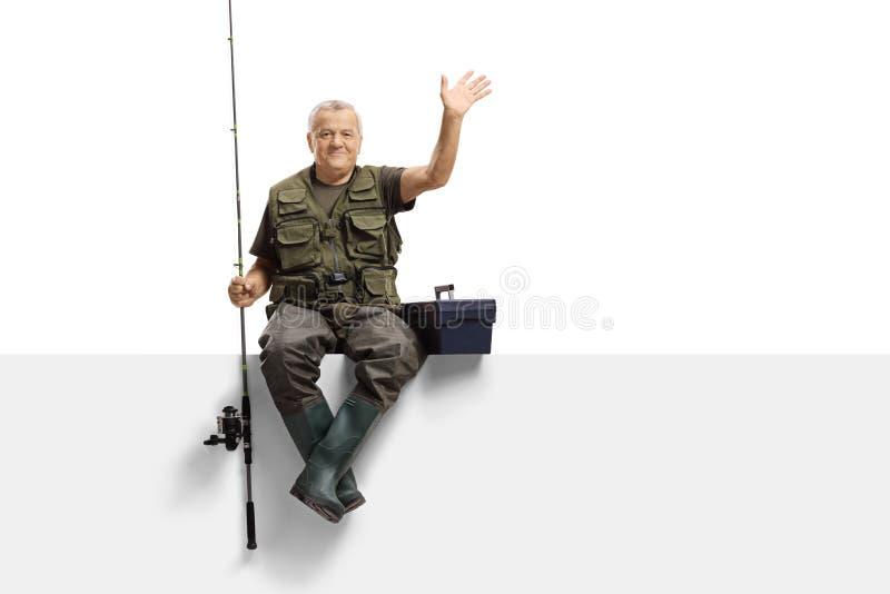 Rijpe visser met een hengelzitting op een paneel en het golven stock afbeeldingen