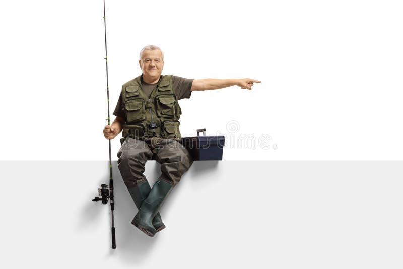 Rijpe visser met een hengelzitting op een paneel en het richten stock afbeelding