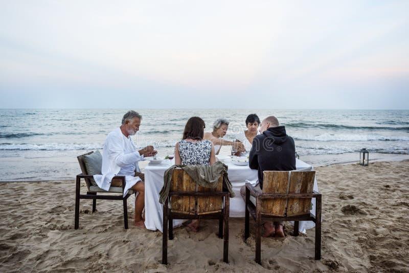 Rijpe vrienden die een dinerpartij hebben bij het strand royalty-vrije stock afbeelding
