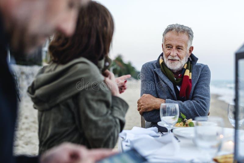 Rijpe vrienden die een dinerpartij hebben bij het strand royalty-vrije stock foto's