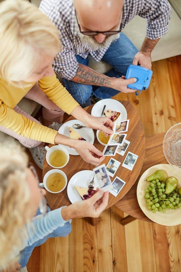 Rijpe vrienden die polaroid op beelden letten stock afbeelding
