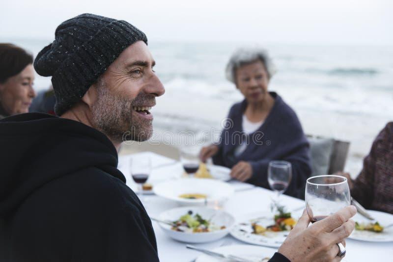Rijpe vrienden die wijn drinken bij het strand stock foto