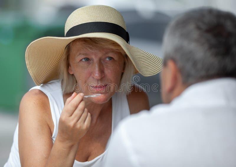 Rijpe vrouw in buitenkoffie stock afbeeldingen