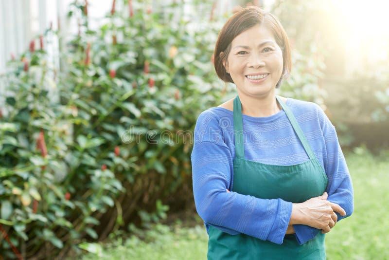 Rijpe vrouw in de tuin stock afbeeldingen