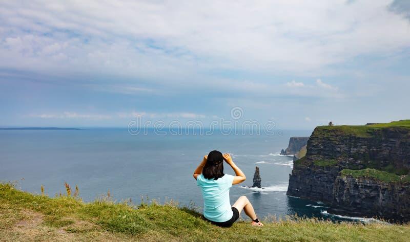 Rijpe vrouw die de klippen en de oceaan in Ierland bewonderen royalty-vrije stock foto