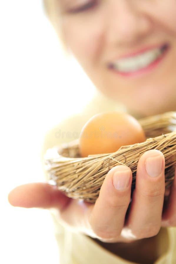 Rijpe vrouw die een nest met een ei houdt stock afbeeldingen