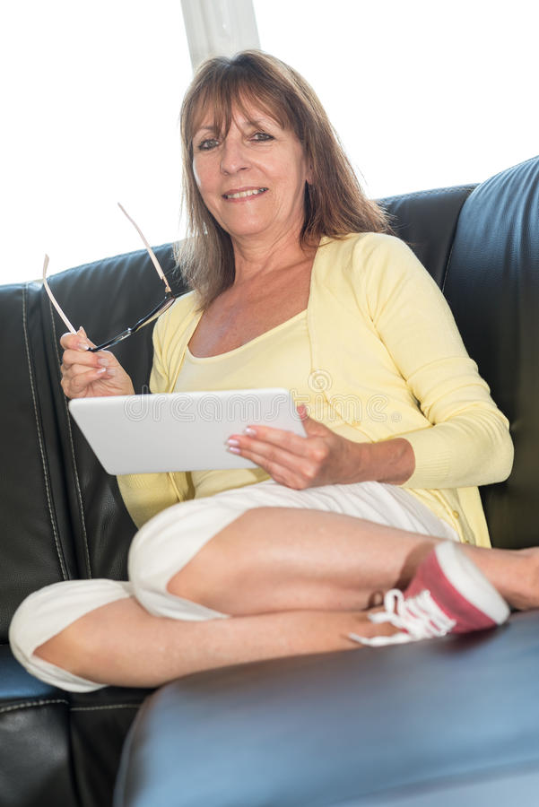 Rijpe vrouw die een tablet gebruiken stock fotografie