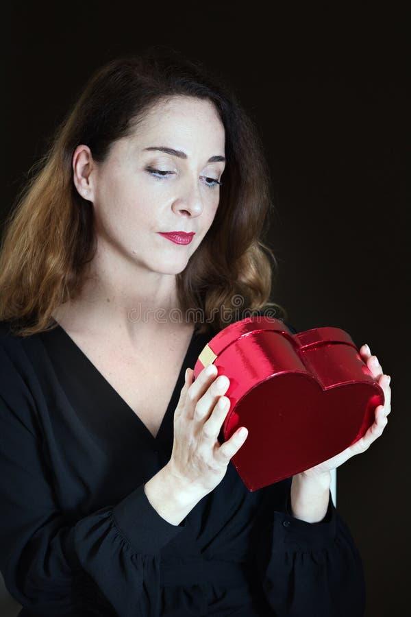 Rijpe vrouw die in haar jaren '40 denken de doos van haar huidige, verwachtende blik, nieuwsgierigheid kijken royalty-vrije stock fotografie