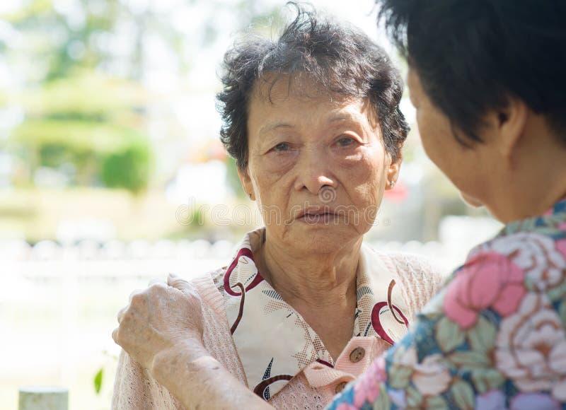 Rijpe vrouw die haar schreeuwende oude moeder troosten royalty-vrije stock afbeelding