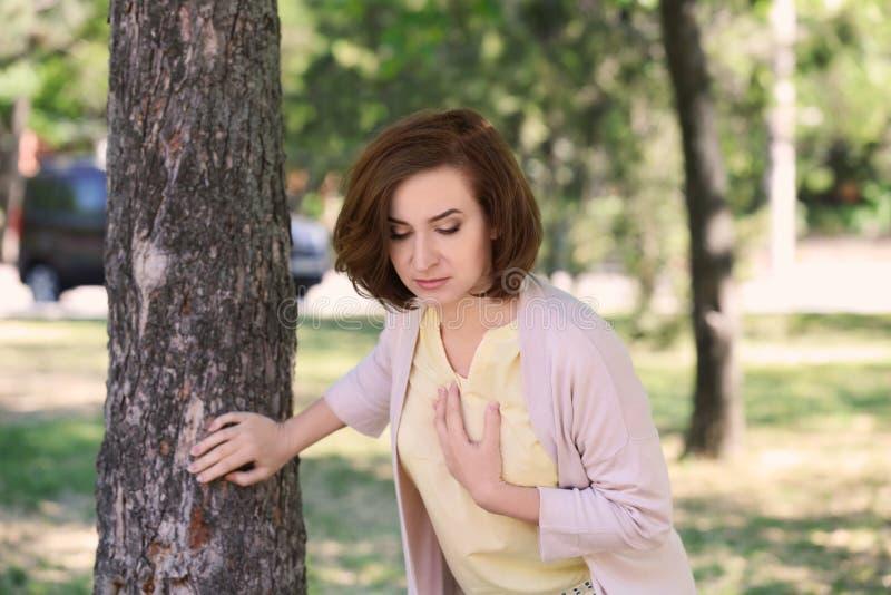 Rijpe vrouw die hartaanval hebben dichtbij boom in groen park royalty-vrije stock foto's