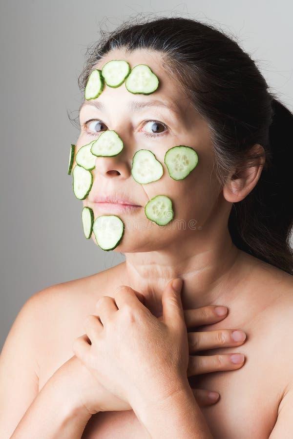 Rijpe vrouw die kosmetisch masker maken stock fotografie