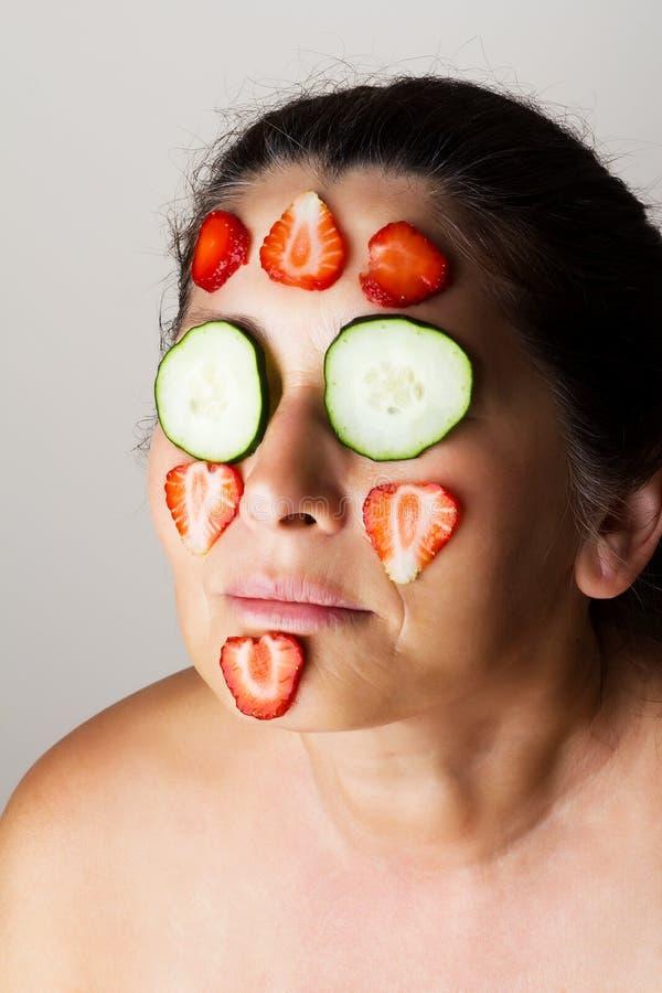 Rijpe vrouw die kosmetisch masker maken royalty-vrije stock afbeeldingen