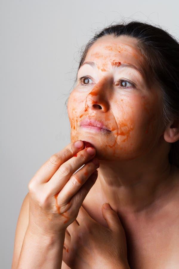 Rijpe vrouw die kosmetisch masker maken stock foto