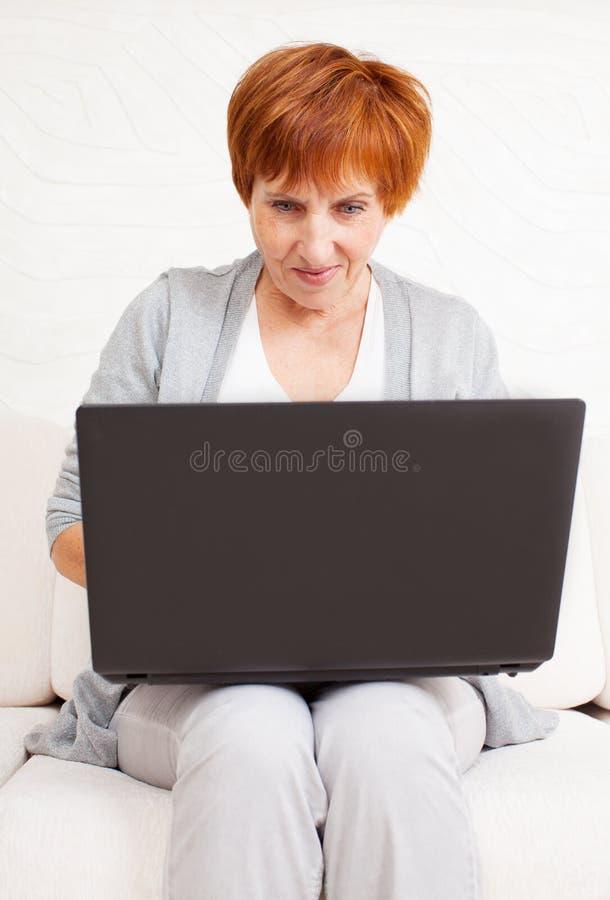 Rijpe vrouw die laptop bekijken royalty-vrije stock afbeeldingen