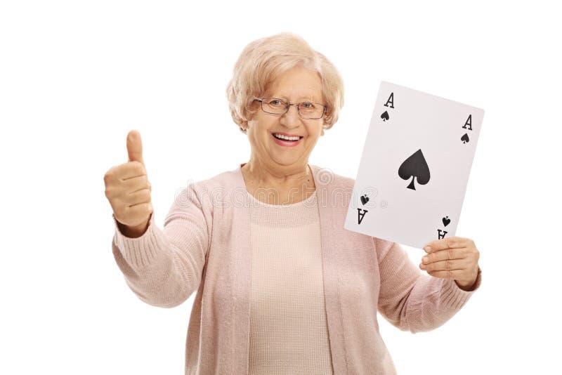 Rijpe vrouw die met aas van spadeskaart duim omhoog maken stock foto