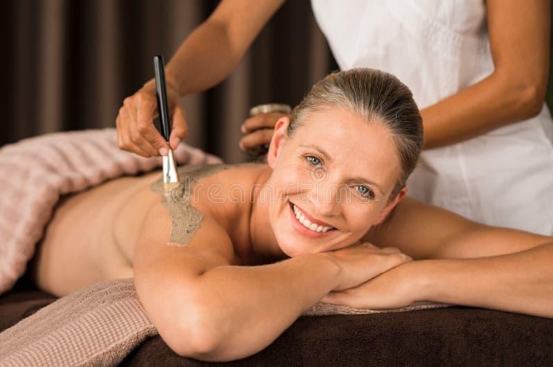 Rijpe vrouw die modder van massage genieten stock afbeelding