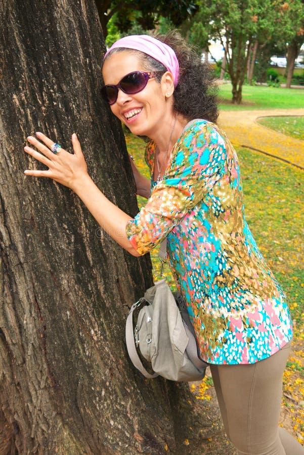Rijpe vrouw die op boom leunt stock fotografie