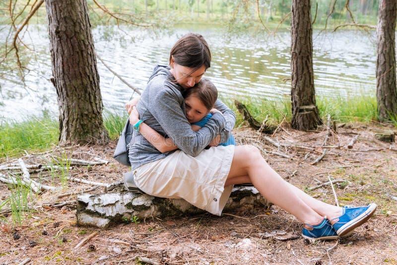 Rijpe vrouw die op middelbare leeftijd haar dochter in het bos koesteren aan haar borst royalty-vrije stock afbeeldingen