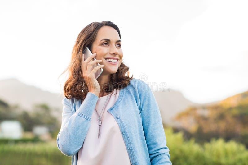 Rijpe vrouw die op telefoon spreken royalty-vrije stock afbeeldingen